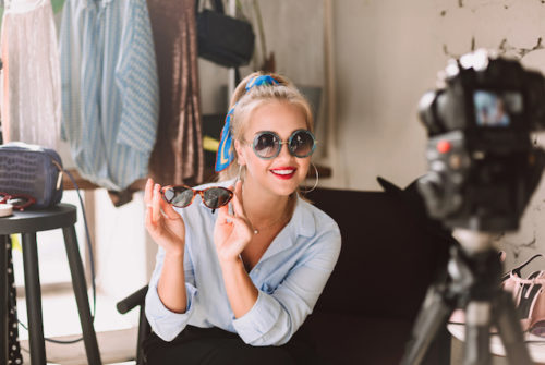 Beautiful smiling fashion blogger in sunglasses happily looking in camera recording new fashion video for vlog with clothes rack on background